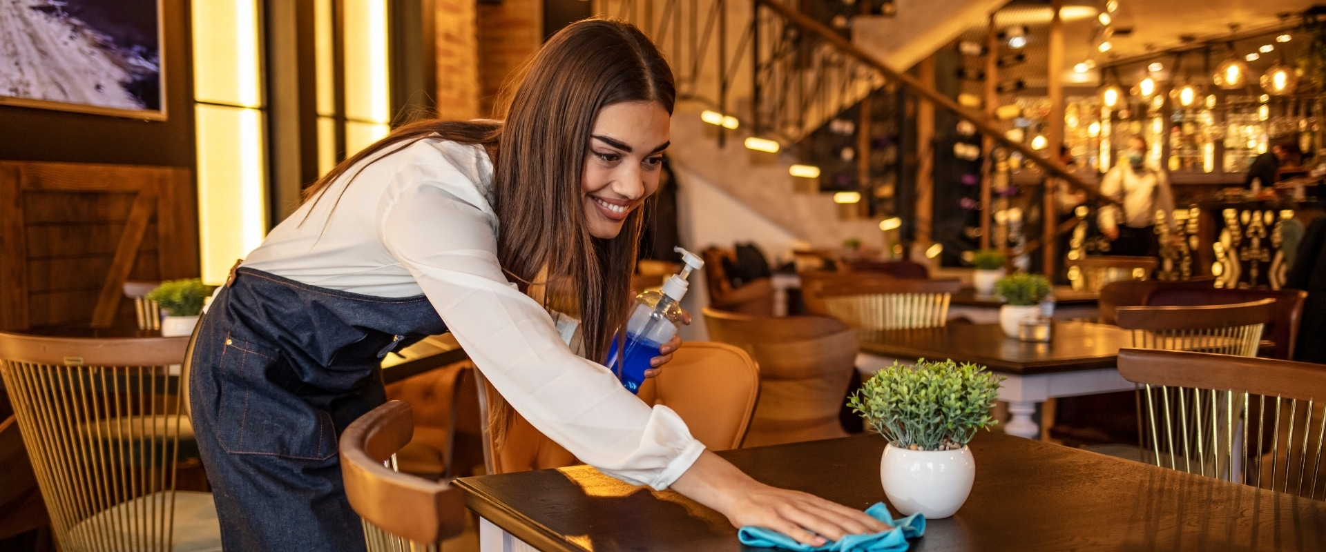 cleaner cleaning tables in a restaurant