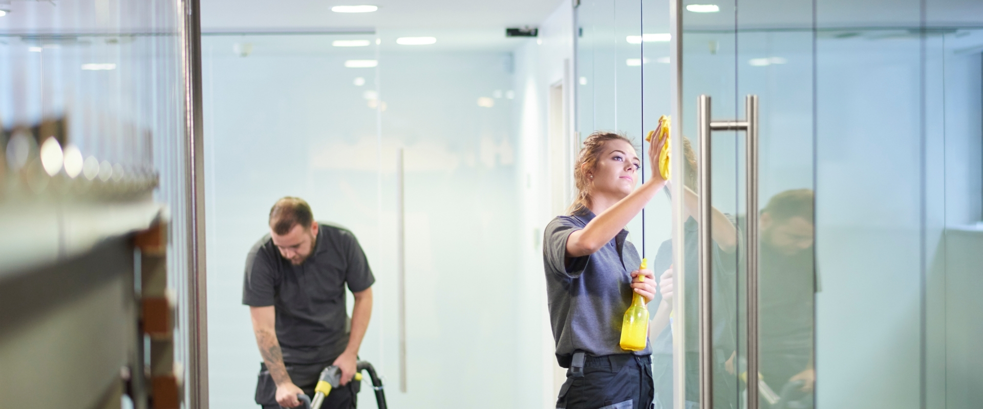 picture of a man and woman cleaning a commercial building entrance
